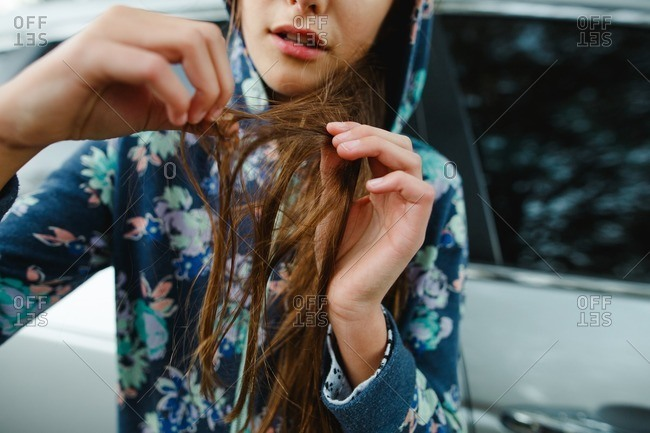 Tween girl leaning on a car undoing a knot from her hair