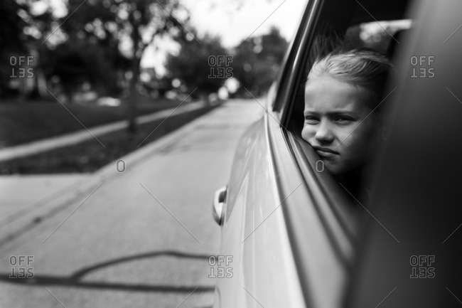 Little girl looking out a car window