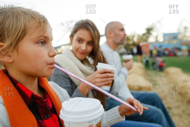 Family with hot drinks sitting on bales of hay