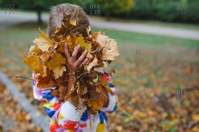 Little girl holding leaves in front of her face