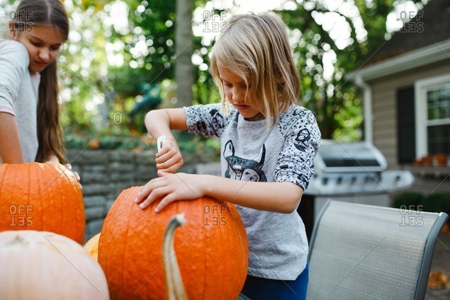 Girls scooping insides out of pumpkins