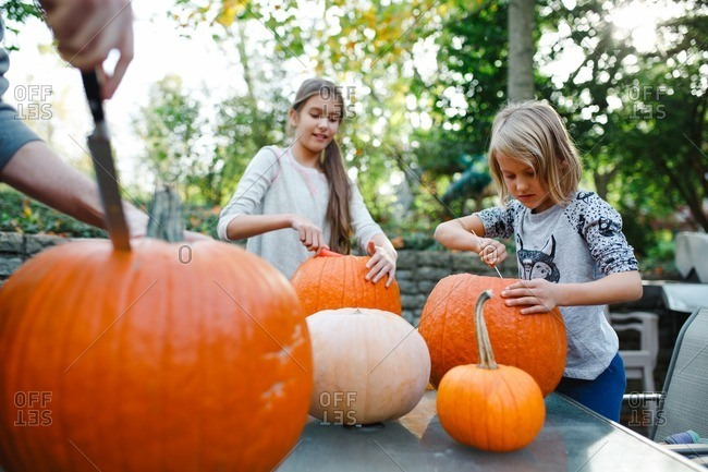 Siblings scooping insides out of pumpkins