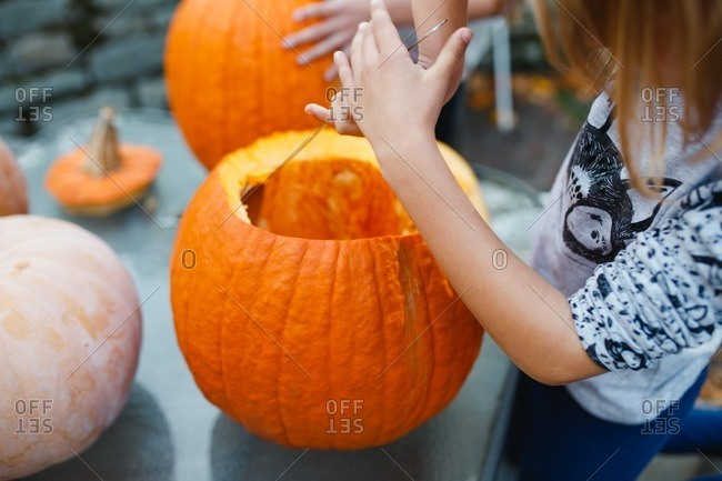 Little girl carving a pumpkin