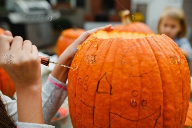 Little girl carving a face on a pumpkin