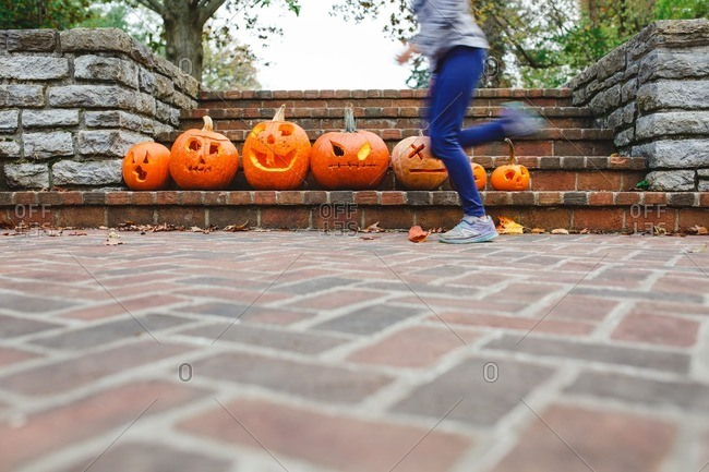 Little girl running in front of jack-o-lanterns