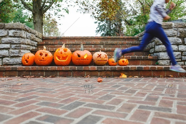 Little girl leaping in front of jack-o-lanterns