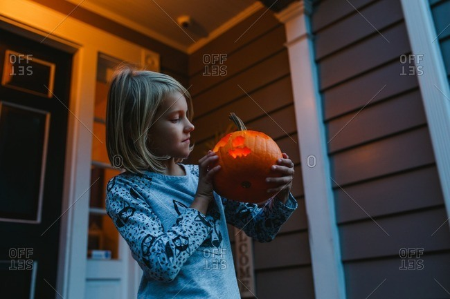 Little girl holding and looking at a jack-o-lantern