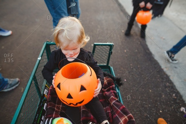Toddler girl in a wagon looking into her pumpkin bucket