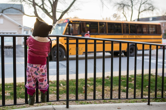 Girl watching a school bus