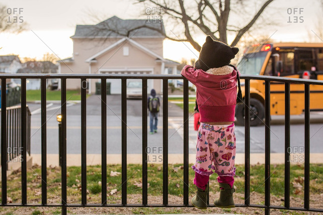 Girl watching boy go to school bus