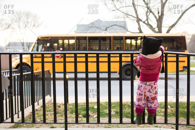 A girl watching a school bus
