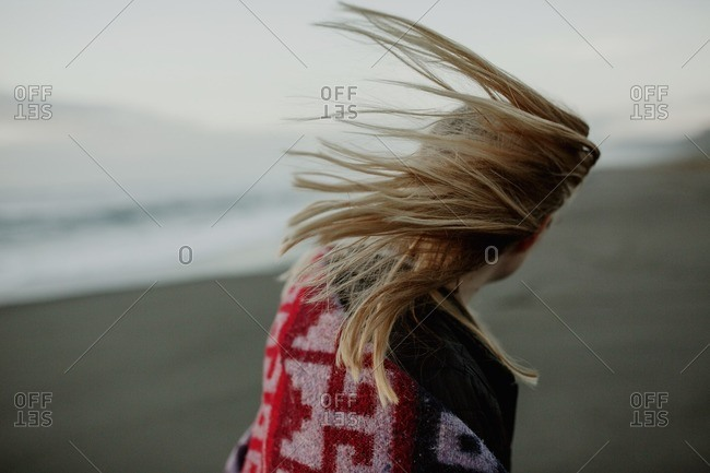 Woman with windblown hair on a beach at dawn