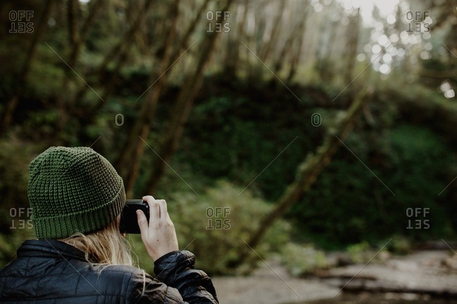 Woman in a forest taking a photograph