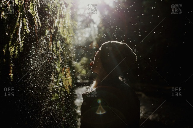 Woman standing in a forest catching water drops on her tongue