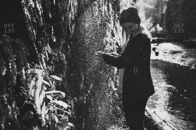 Woman standing under a dripping waterfall in a forest