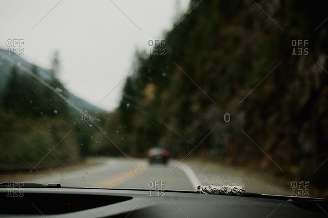 Smudge stick on the dashboard of a moving vehicle on a mountain highway