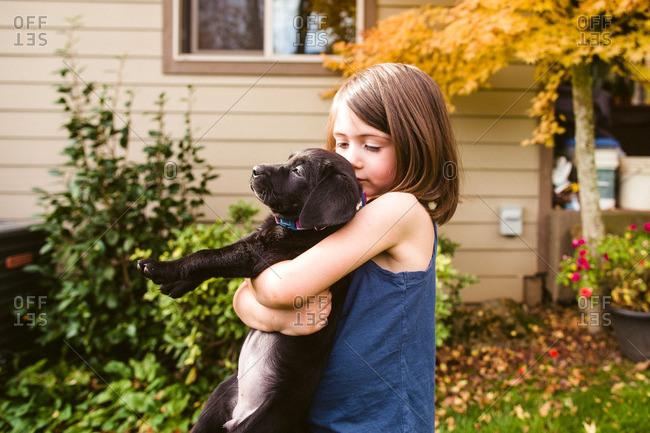 Little girl hugging a black lab puppy