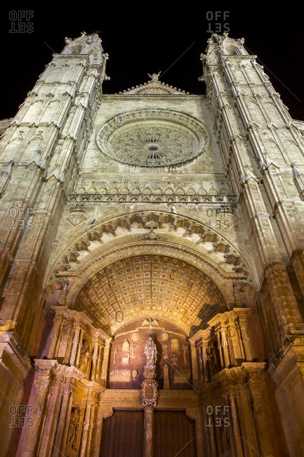 Facade of an elaborately carved church illuminated at night