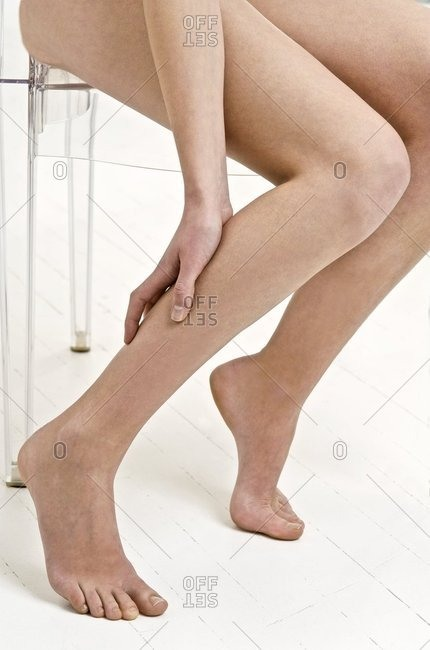 Woman holding her sore calf