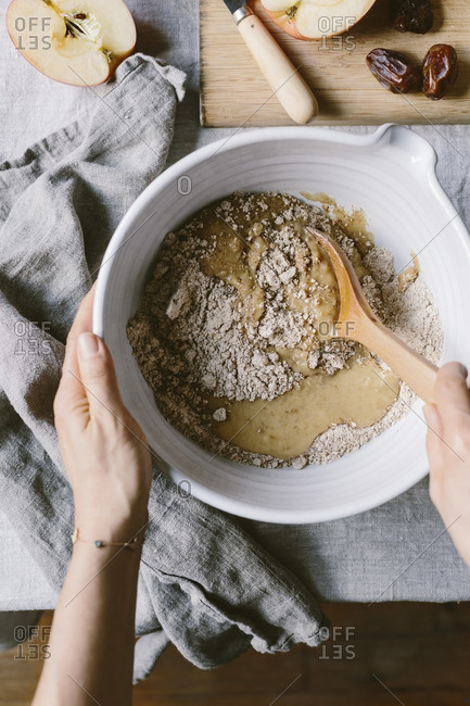 A woman is photographed as she is folding dry ingredients in to wet ingredients for an apple muffin batter