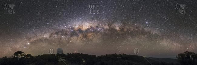 The Milky Way arc setting over the Siding Spring Observatory in Australia with the Anglo-Australian Telescope.