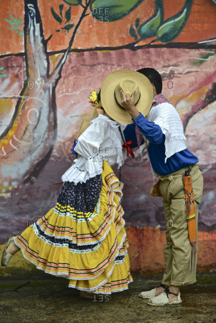 A couple, wearing traditional clothing, kiss behind a hat in Ibague, Colombia.
