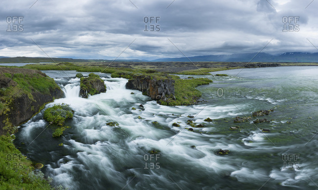 Scenic view of a waterfall at the mouth of the Myrarkvisl river along the northern coast near Husavik.