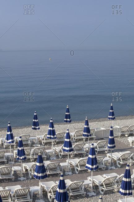 Beach umbrellas on a private beach that lines Quai des Etats-Unis in Nice, France.
