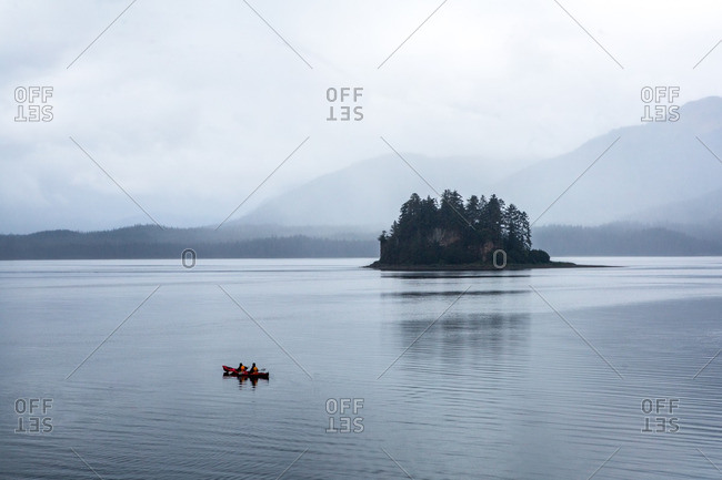 Kayakers in a tandem kayak on a gray morning in southeastern Alaska.