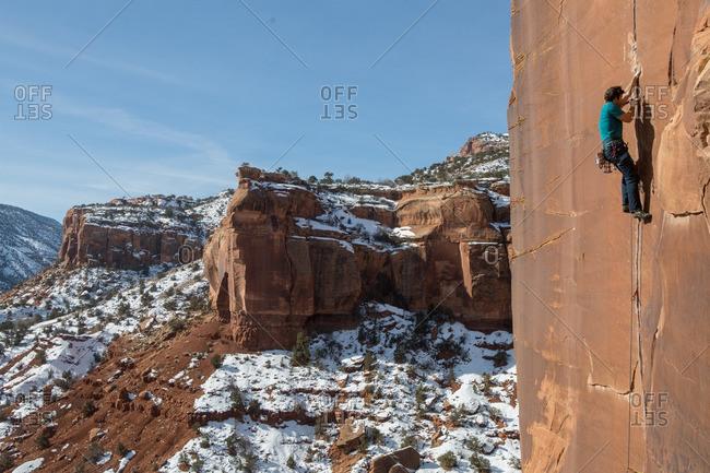A man climbs sandstone cracks in Colorado desert.