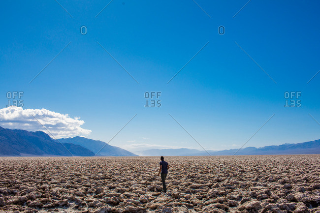 A man walking across the cracked desert plains in Death Valley.