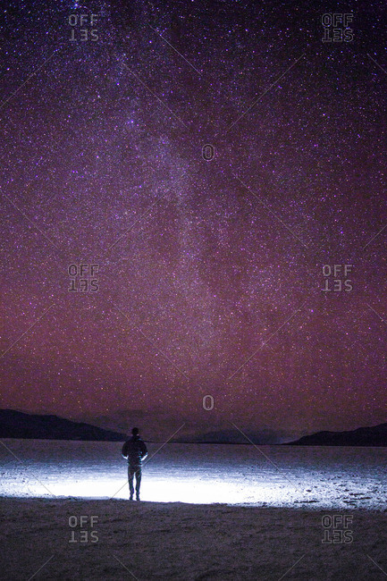 A man standing on the salt flats looking up at the Milky Way.