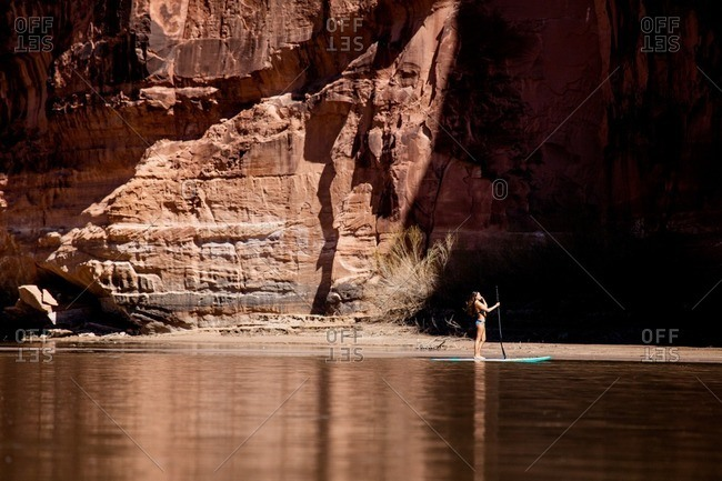 A young woman paddleboarding on the Colorado River in Utah.