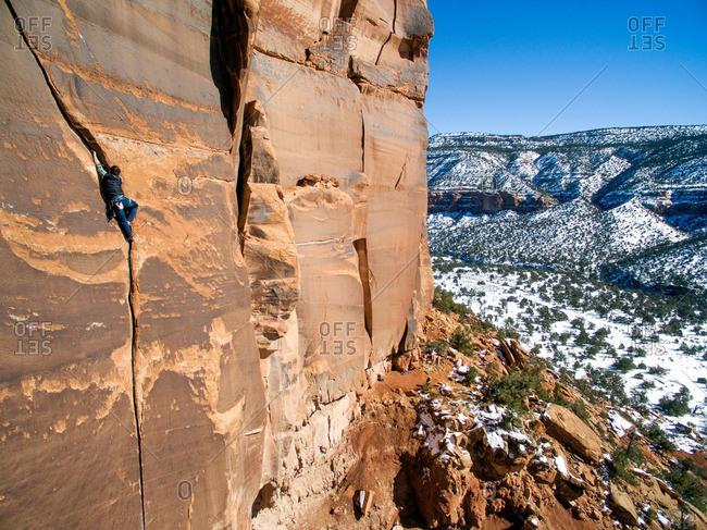 A man climbs sandstone cracks in the Colorado desert.
