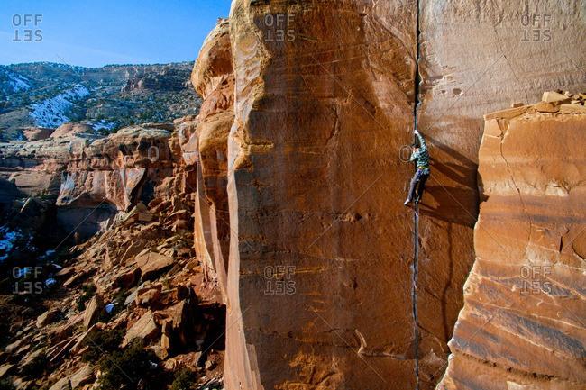 Male climber climbing sandstone cracks in the Colorado desert.