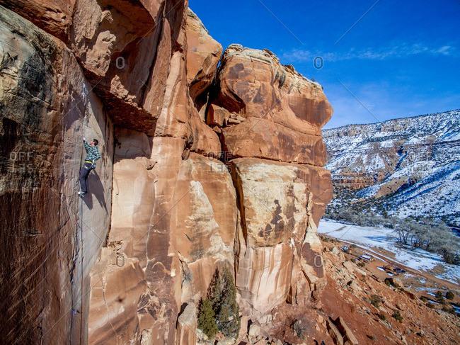 Man climbing sandstone cracks in the Colorado desert.