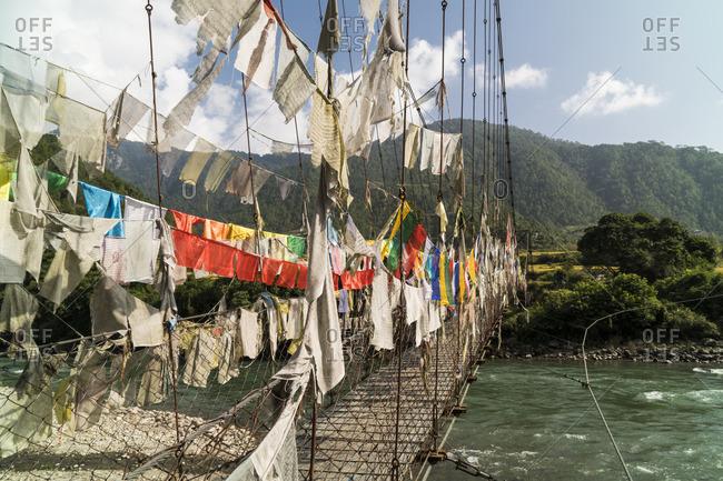 Prayer flags on a bridge over the Mo Chhu river in Punakha, Bhutan.