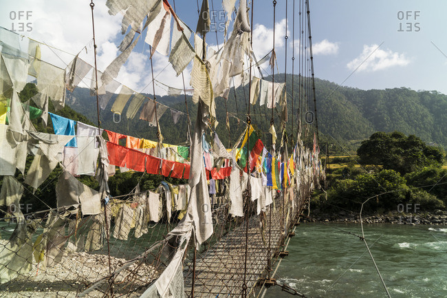 Prayer flags on a bridge over the Mo Chhu river in Punakha, Bhutan.