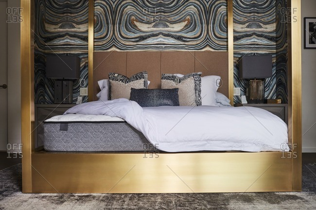 Gold four-poster bed in modern bedroom