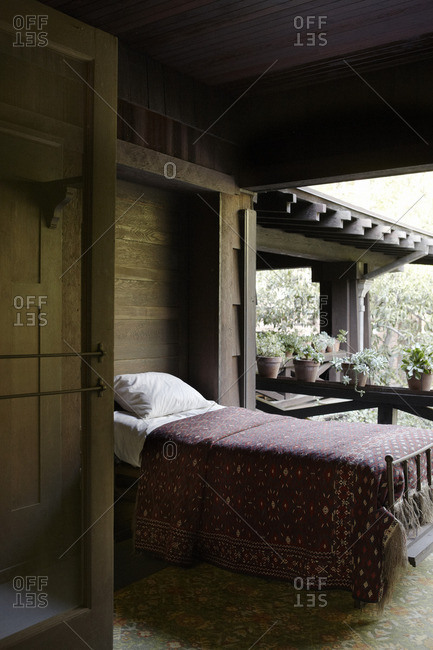Bed on a screened sleeping porch of rustic home