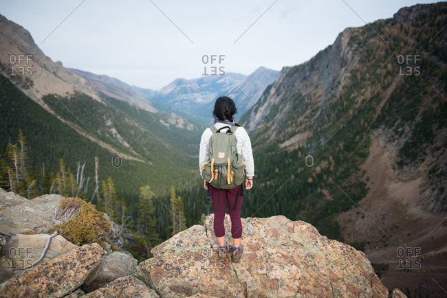 Person standing on a rocky outcrop and looking off into the distance at a scenic overlook in the mountains