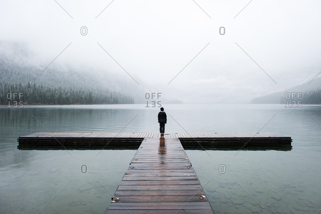 Person standing at the end of a wooden dock on a mountain lake