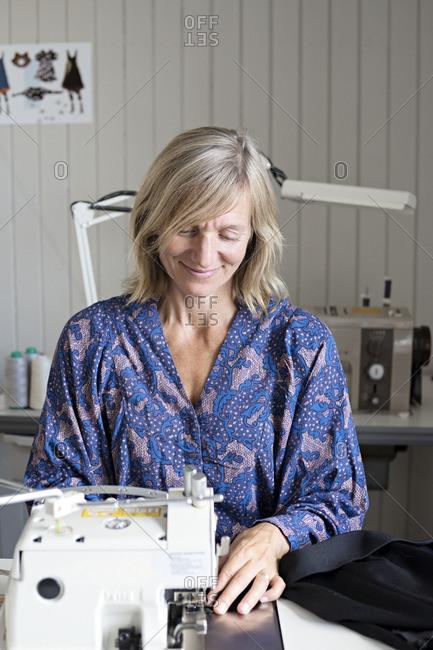 Tailor sewing in workshop - Offset