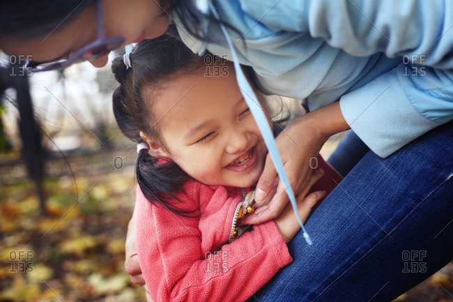 Cute young girl with mother in a park during autumn