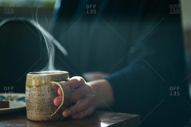 Hand on steaming mug