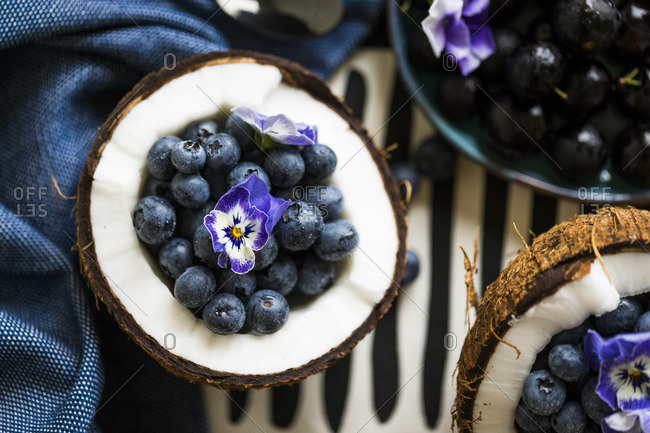 Blueberries in a halved coconut with a pansy flower