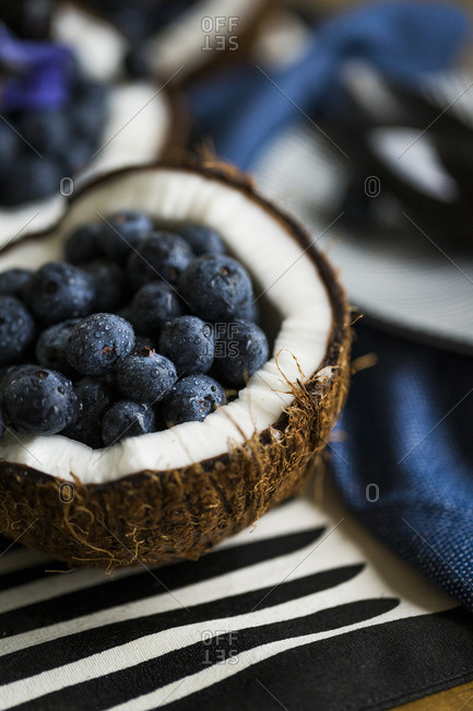 Fresh blueberries in a coconut half and cloth napkin