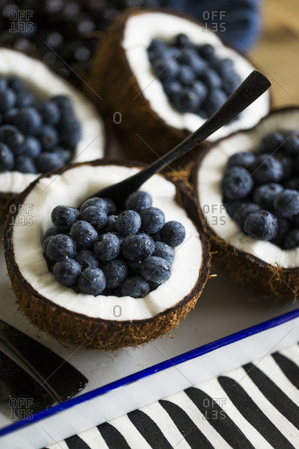 Spoon in a halved coconut filled with fresh blueberries