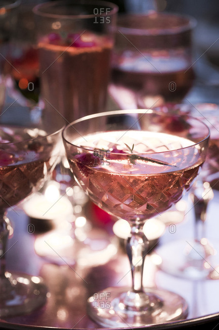 Pink champagne in a variety of cut crystal glasses garnished with flowers