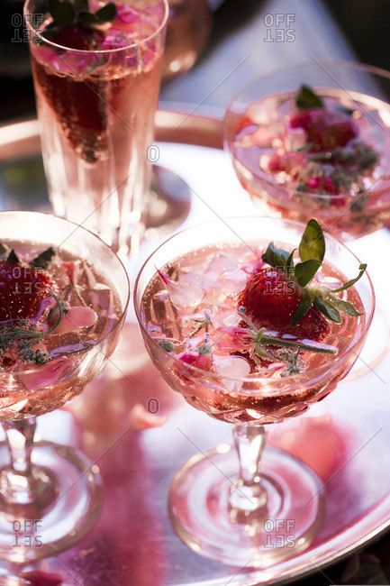 Glasses of pink champagne garnished with flowers and strawberries